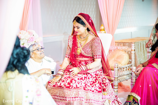 Enchanting Indian bride sitting at wedding ceremony.