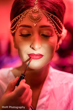 Gorgeous maharani being assisted with hair and makeup