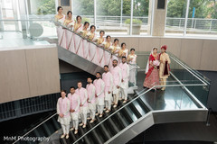 Groomsmen and bridesmaids pose with the Indian couple