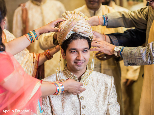 Indian groom getting help to get ready