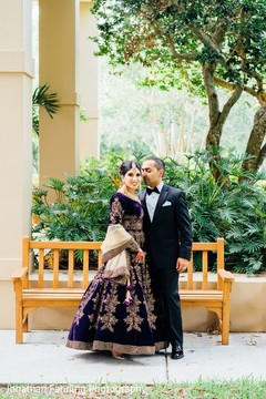 Elegant Indian bride and groom posing with their wedding reception outfits.