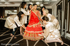 Enchanting Indian bride getting help by bridesmaids getting ready.