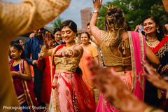 Indian bride and bridesmaids dancing at the baraat celebration.
