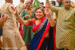 Indian family members dancing at the baraat celebration.