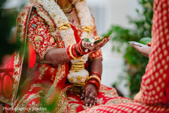 Indian couple holding items during wedding ceremony ritual.