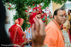 Indian bride and groom being thrown red roses petals during ceremony.