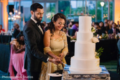 Indian wedding cake cutting fun moment.