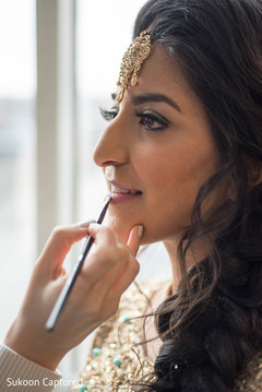Indian bride getting makeup last touch ups for her wedding reception.