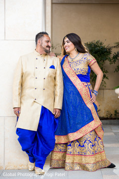 Beautiful detail of the sari and sherwani worn by the Indian couple