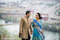 Joyful Indian couple hold hands as the photo shoot continues
