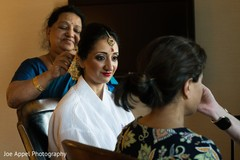 Maharani being assisted with the bridal ornaments