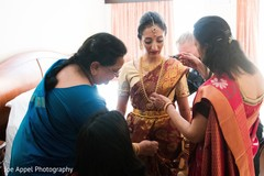 Indian bride being assisted with the beautiful sari and bridal jewelry