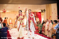 Joyful Indian couple hold hands as the Indian wedding ceremony ends