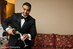 Indian groom pours some champagne prior to the ceremony