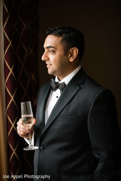 Indian groom posing for pictures holding his drink