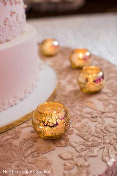 White and golden Indian wedding cake decor.