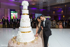 Sweet indian wedding cake cutting moment.