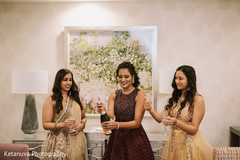 Maharani opening a champagne bottle with the bridesmaids