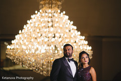 Indian bride and groom pose for pictures at the venue