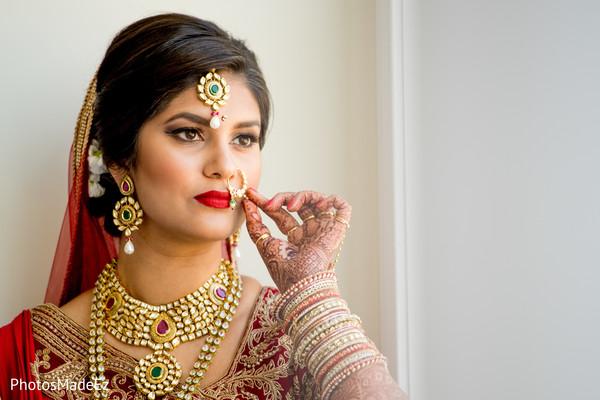 Enchanting Indian bride holding her Nose ring.