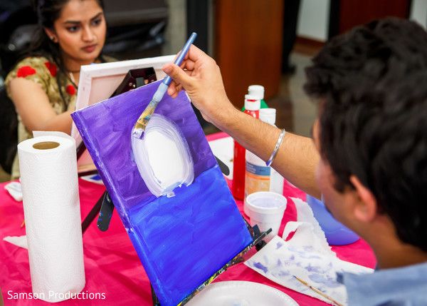 Guests enjoy the painting process before the Indian wedding