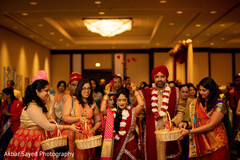 Cheerful guests celebrate the Indian couple with rose petals