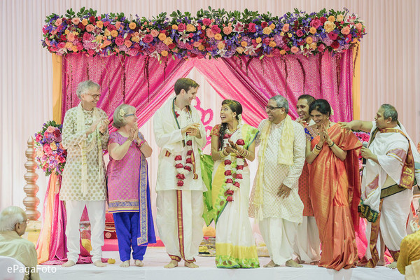 Joyful Indian bride and groom walking out of wedding ceremony.