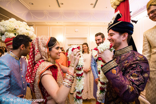 Maharani and Raja holding the flower garland during the ceremony