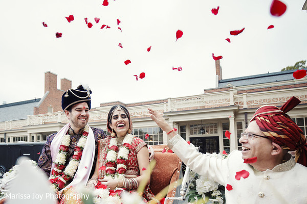 Cheerful Indian couple smile as a special guest throws rose petals