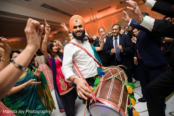 Guests dance to the dhol at the Indian wedding reception