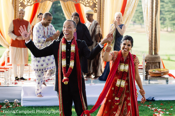 Cheerful Indian newlyweds wave at the guests
