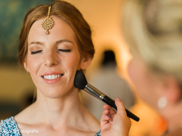 Adorable indian bride getting her makeup done