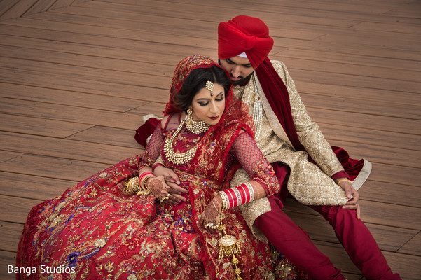 Indian bride and groom posing outdoors on their ceremony outfits.