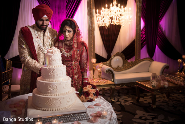 Indian couple cutting the delicious wedding cake