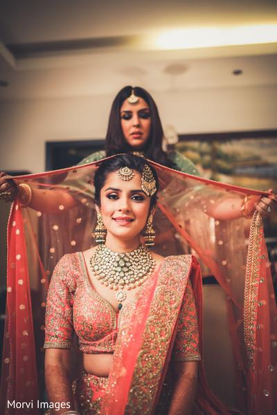 Indian bride getting help to put her wedding Ghoonghat veil on.