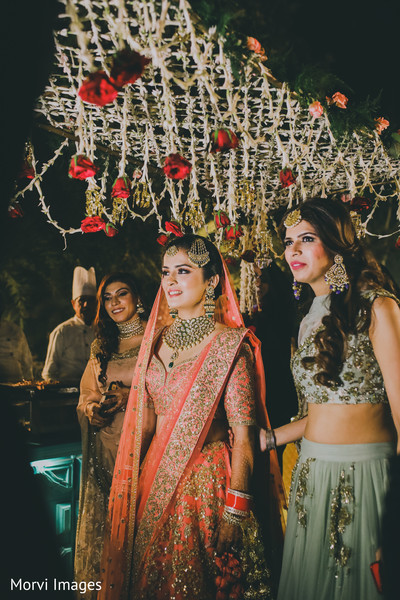 Glamorous Indian bride walking  in with bridesmaids.