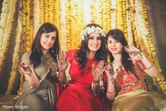 Indian bride and bridesmaids showing mehndi art.