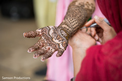 Mehndi artist working on the bride's arm
