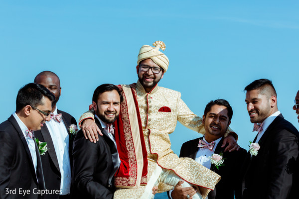 Groomsmen lift the Indian groom during the Baraat