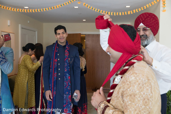 Indian groom being assisted with the pagri