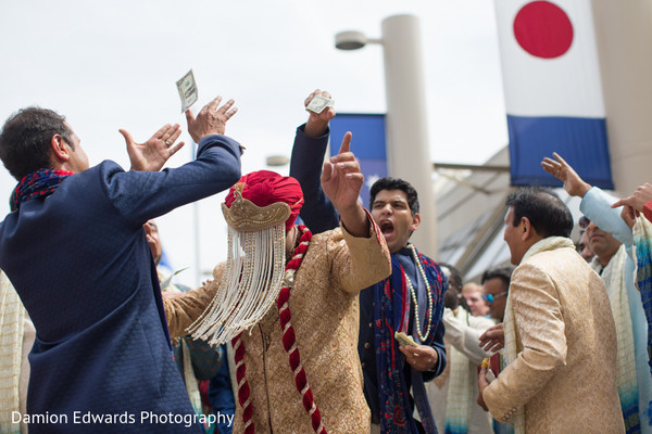 Cheerful Indian groomsmen throw money at the raja