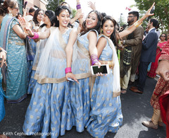 Indian bridesmaids posing for pictures during the baraat