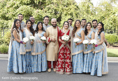 Indian newlyweds posing with bridesmaids and groomsmen