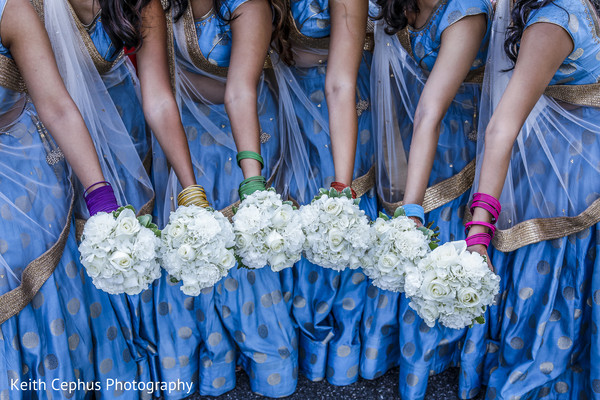 Indian bridesmaids pose for pictures with the bouquets