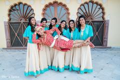 Fun capture of beautiful bridesmaids holding the raja