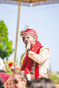 Indian groom holding ceremonial coconut.