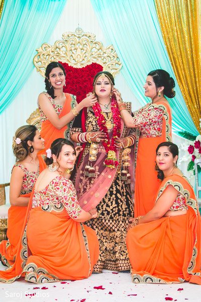 Sweet Indian bride with bridesmaids posing for photo.