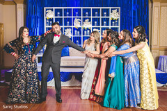 Fun capture of Indian bride and groom with bridesmaids.