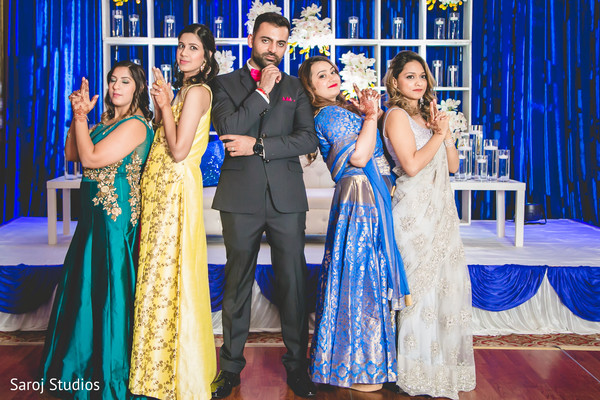 Indian groom with bridesmaids James Bond look photo.