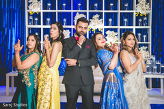 Creative capture of Indian groom with bridesmaids.